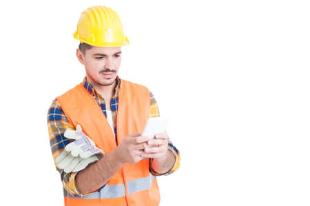 Handsome engineer typing something on his white smartphone isolated on white with copy space