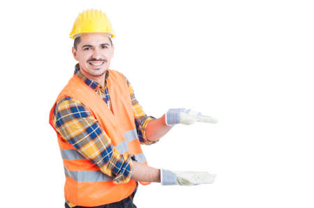unifrom: Cheerful constructor showing something small with his hands as scale or size concept with advertising area isolated on white
