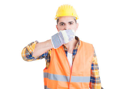 Young constructor covering his mouth with hands or making the speak no evil gesture isolated on white