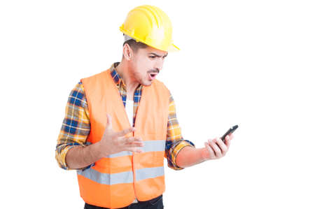rage: Furious young constructor yelling and showing rage while looking at his mobile phone because of a problem on white background Stock Photo