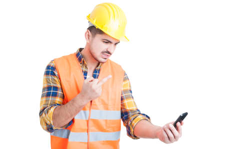 rudeness: Rudeness and obscene gesture concept with young engineer or constructor showing middle finger at cellphone isolated on white