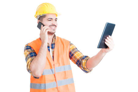 workwear: Male constructor in workwear with modern tablet using cell phone and smiling on white studio background