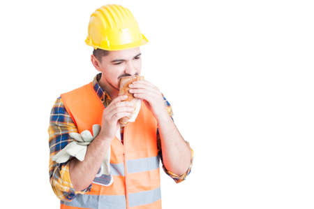 Male constructor with protection helmet is eating a tasty sandwich in his break on white background