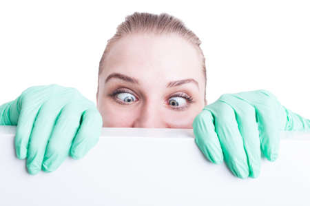 squint: Funny woman doctor holding her eyes crossed  and act silly while covering her face with a blank banner isolated on white Stock Photo
