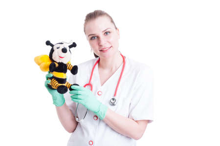 pediatrist: Cheerful woman doctor holding a bee plush toy as trusthworthy doctor concept isolated on white background