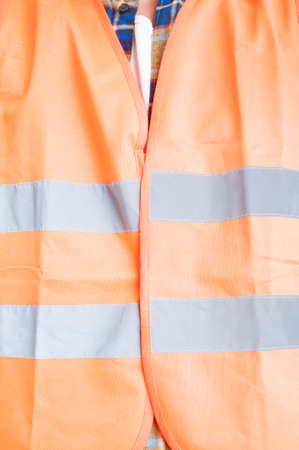 warning vest: Safety construction concept with male engineer wearing orange protection vest with reflective stripes in close-up Stock Photo
