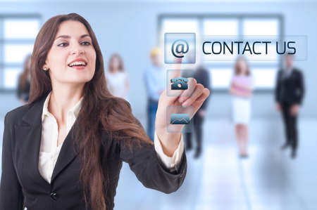 business contact: Contact us concept with business woman pressing transparent futuristic button on digital display or touch screen Stock Photo
