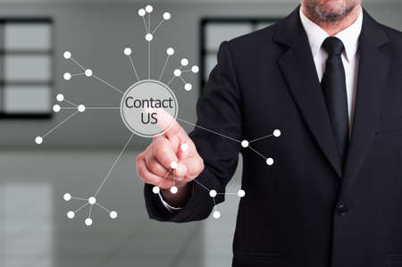 contactus: Business man pressing contact us button on digital transparent screen as company support or assistance feedback concept
