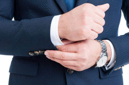 sleeve: Businessman fixing and adjusting white shirt sleeve under blue suit. Rich and expensive concept Stock Photo