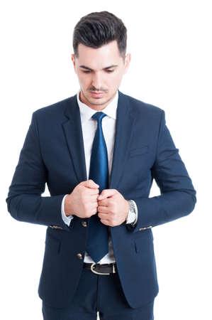 cerrando negocio: Pensive business man wearing elegant blue suit and tie looking down and closing jacket