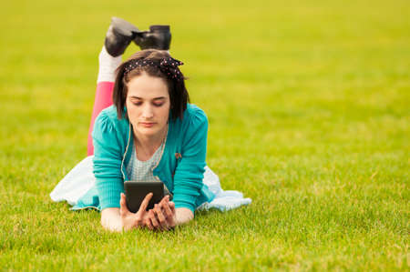 Attractive female using tablet outdoor while sitting on grass and relaxing in her free time
