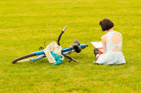 spring green: Beautiful young woman in dress sitting on grass with a book in her hand as back view near vintage bicycle