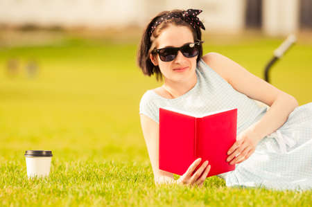 freetime: Close-up of joyful beautiful female sitting with book on grass, wearing sunglasses and smiling outdoor in the park