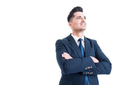 visionary: Visionary businessman banker or broker looking up smiling with arms crossed isolated on white background