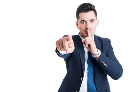 shush: Confident businessman making keep a secret and silence gesture isolated on white background