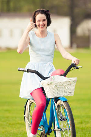 thumbup: Joyful hipster doing like or thumbup gesture in the park while riding the bicycle Stock Photo