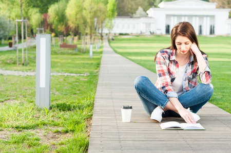 comfortable: Young female having a coffee break outside on sunny day and reading a book in the park