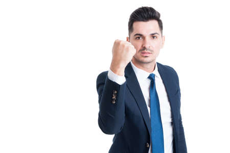 Handsome and aggresive young manager threatening by showing the fist isolated on white background