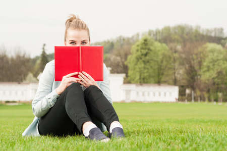 copy paste: Young cheerful female hiding her face with book and relaxing outside in the park with copy paste