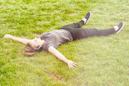 arms wide open: Young beautiful woman lying on grass with arms wide open and listening music on headphones on sunny day