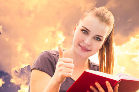 thumbup: Close-up portrait of attractive smiling girl reading a book and showing thumbup ok like gesture in the park Stock Photo