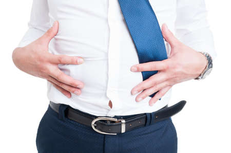 Businessman in closeup holds his stomach because of bloating as abdominal pain and problem concept isolated on white Standard-Bild