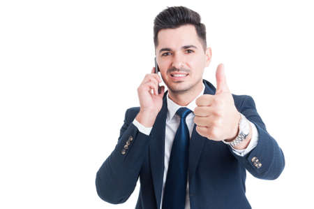 trustful: Young successful businessman talking on smartphone and showing thumb up isolated on white background