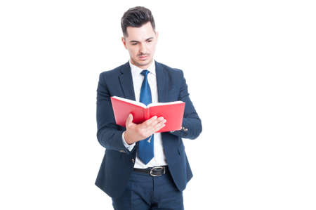 law suit: Young attractive lawyer in elegant suit holding and reading a law book isolated on white background Stock Photo