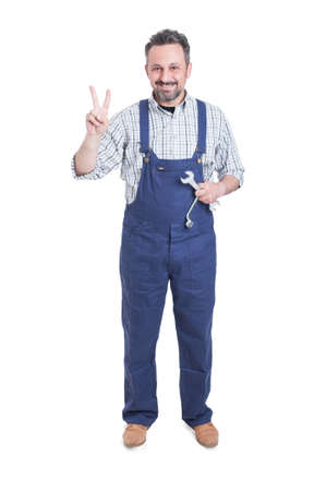 studio happy overall: Full body of smiling mechanic with wrench or spanner doing victory gesture isolated on white