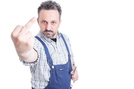 insulting: Aggressive mechanic in overall holding tools and making insulting gesture with copy space area isolated on white