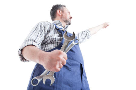 shot: Hero shot with young mechanic pointing finger up and holding spaneer isolated on white background