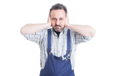 hands covering ears: Young attractive mechanic covering his ears with hands as hear no evil concept isolated on white Stock Photo