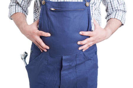 bloating: Discomfort and bloating concept with young mechanic holding his belly in close-up isolated on white background