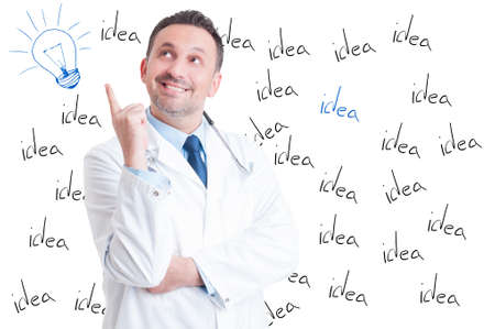 revelation: Excited handsome successful doctor pointing a great idea or having a revelation on white background with lightbulb above his head Stock Photo