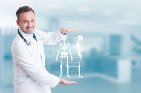 Handsome orthopedist doctor holding skeleton model hologram on his hands and smiling as healthy bone concept with copyspace