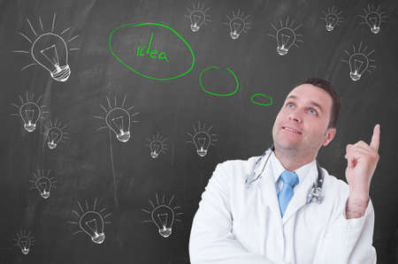 coming up with: Happy young doctor coming up with an idea or solution for medical treatment with bubble and light bulb behind him
