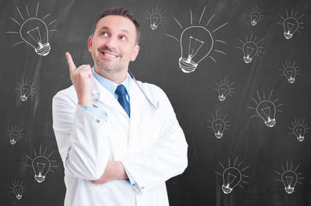 new medicine: New idea in medicine with cheerful confident doctor pointing finger up and smiling on black background with drawn lightbulb
