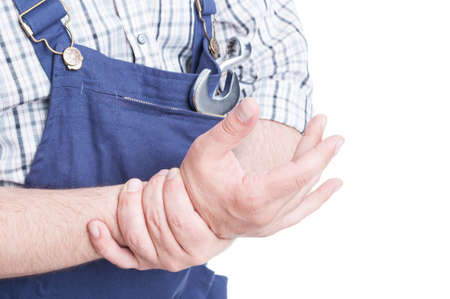 Close-up of repairman in blue overalls holdig his wrist in pain as hand injury concept isolated on white