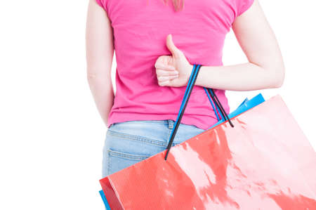 thumbup: Back view of woman hand doing thumbup or like gesture and holding shopping bags isolated on white background