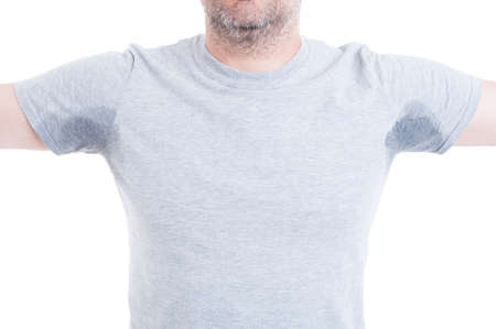 Man with both arms raised and excessive sweat stains on grey t-shirt isolated on white as hyperhidrosis concept Standard-Bild