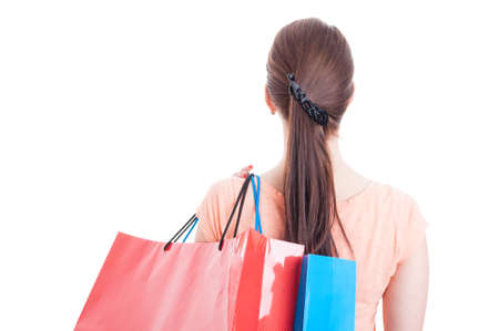 shoulder carrying: Back view of woman carrying shopping bags on shoulder isolated on white background with text area