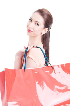 shoulder carrying: Portrait of female model carrying big shopping bags on her shoulder and smiling happy isolated on white background Stock Photo