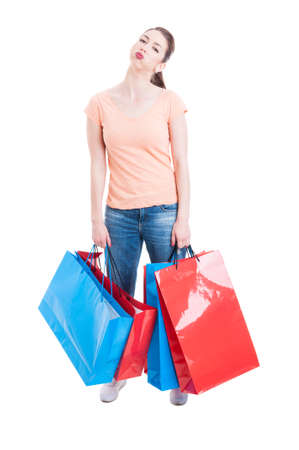 carrying heavy: Young woman carrying heavy shopping bags feeling tired and exhausted isolated on white background Stock Photo