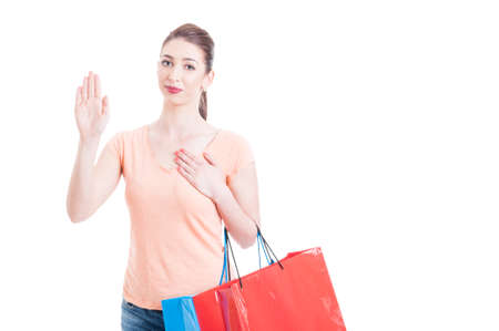 promising: Young lady with shopping bags showing swearing or promising gesture concept isolated on white background with advertising area Stock Photo