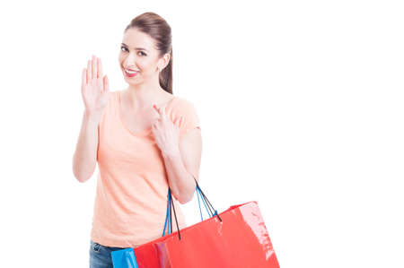 promising: Lady carrying shopping bags swearing or promising with fingers crossed concept isolated on white background with copy space