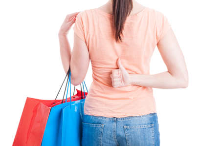 thumbup: Female holding shopping bags and showing thumb-up like or approval gesture behind back isolated on white whit copy text space Stock Photo