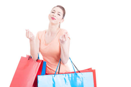 spending money: Woman with shopping bags making spending money gesture and feeling pleased or accomplished isolated on white with advertising area Stock Photo