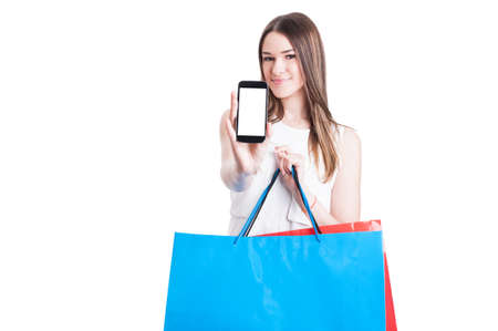 happy shopper: Happy shopper with shopping bags showing a blank smartphone screen with copyspace isolated on white background Stock Photo