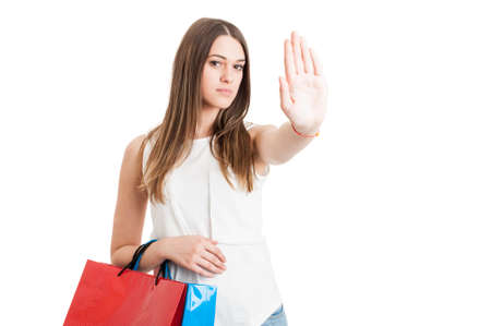 spending money: Young serious customer with shopping bags making a stop sign with hand as no more spending money on shopping concept isolated on white