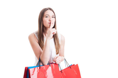 Attractive pretty shopaholic with shopping bags making a silence gesture as quiet or shush concept isolated on white studio background with copyspace